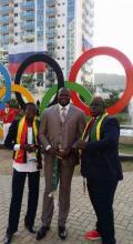 Frank Elemba devant les anneaux olympiques avec Cécilia Bouélé et monsieur Tamba, le directeur technique du Comité olympique congolais